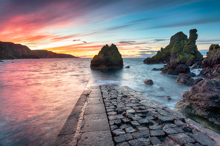 A fiery red sunset over Pettico Wick Bay at St Abbs near Eyemouth on the east coast of Scotland