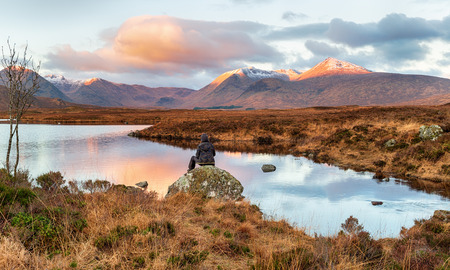 A woman hiker sitting on a rock watxhing the sunrise at Lochan na h Achlaise at Glencoe in the Scottish Highlands