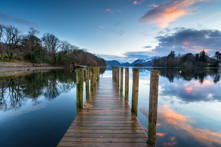 Sunset over a wooden jetty on Derwentwater at Keswick in the Lake District natioal park in Cumbria