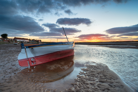 Sunset over a fishing boat at Burnham Overy Staithe a pretty fishing village on the Norfolk Coast
