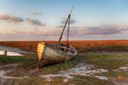 An old beached fishing boat on the marshes at Thornham on the Norfolk coast 免版税图像
