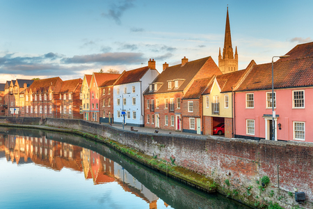 Pretty town houses overlooking the river Yare at Norwich in Norfolk with the cathedral spire in the background
