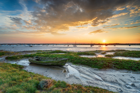 An old boat in the salt marsh at West Mersea a tidal island near Colchester on the Esssex coast