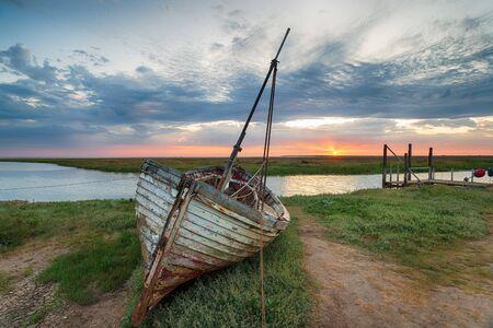 Sunrise over abandoned fishing boat on the shore at Thornham on the north coast of Norfolk
