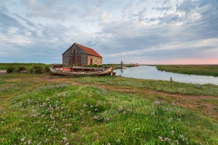Sunrise over the old harbour and boats at Thornham on the north coast of Norfolk