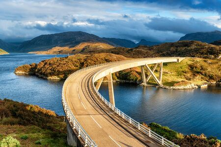 The curved Kylesku Bridge which crosses Loch a' Chàirn Bhàin in the Highlands of Scotland and forms part of the North Coast 500 scenic driving route Reklamní fotografie
