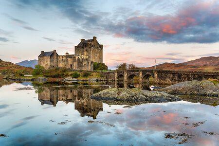 Sonnenaufgang über Eilean Donan Castle spiegelt sich in den stillen Gewässern des Lochs bei Dornie in den Highlands von Schottland