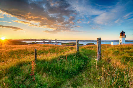 Beautiful sunset over the lighthouse and coastguard cottages at Arnish Point near Stornoway on the Isle of Lewis in the Outer Hebrides of Scotland Stock fotó