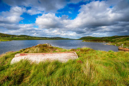 An upturned boat on the shores of Loch Erisort near Balallan on the Isle of Lewis in the Western isles of Scotland Stock fotó