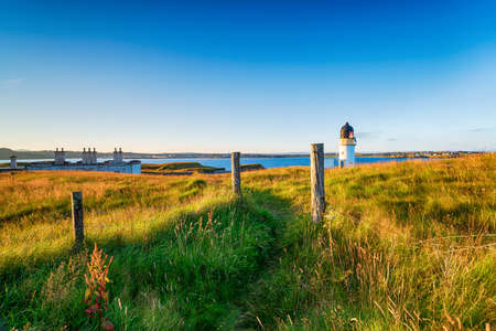 The lighthouse and coastguard cottages at Arnish Point on the entrance to Stornoway harbour on the Isle of Lewis in Scotland