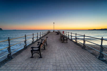 Sunrise over the Banjo Pier on the beach at Swanage on the Dorset coast Stock fotó