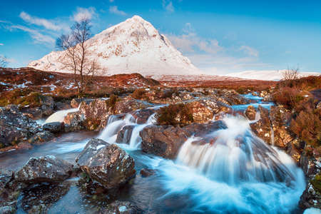 Snow topped mountains and waterfalls at Glen Etive in the Highlands of Scotland