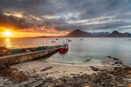Dramatic sunset over the quay at Elgol on the Isle of Skye in the Highlands of Scotland