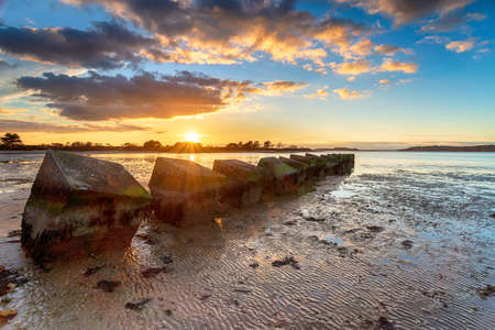 Beautiful sunset over old WWII tank traps in Bramble Bush Bay at Studland on the Isle of Purbeck in Dorset