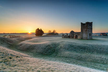 Frosty sunrise over the old church at Knowlton near Wimborne in the Dorset countryside