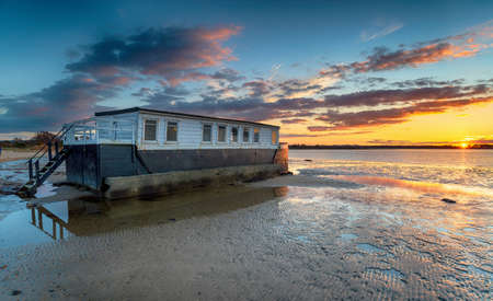 Dramatic sunset over a houseboat in Bramble Bush Bay at Studland on the Dorset coast