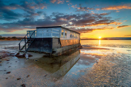 Stunning sunset over an old houseboat moored at Bramble Bush Bay at Studland on the Isle of Purbeck