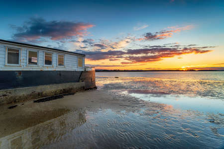 Sunset over an old boat on Bramble Bush Bay at Studland in Poole Harbour on the Dorset coast Stock fotó