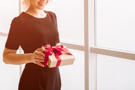 La bella ragazza in possesso di un regalo o una sorpresa in mano