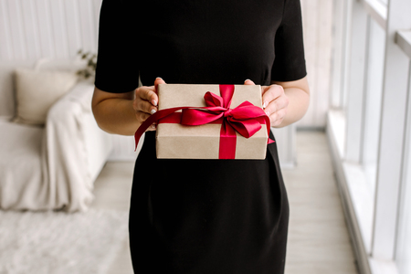 womens day: The beautiful girl holds a gift or a surprise in hand