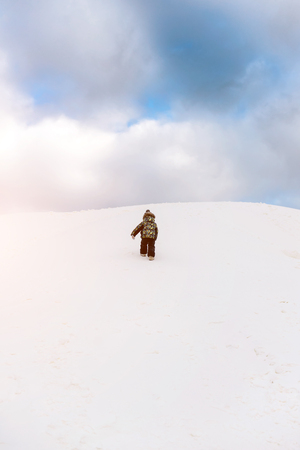 rises: The little boy rises uphill in the winter