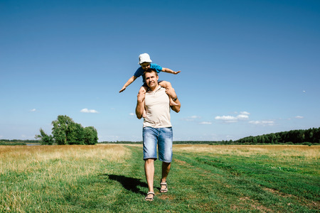 family with two children: the father and the son walk in the country outdoors Stock Photo