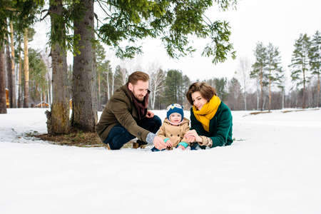 palle di neve: the family molds snowballs against a winter forest Archivio Fotografico