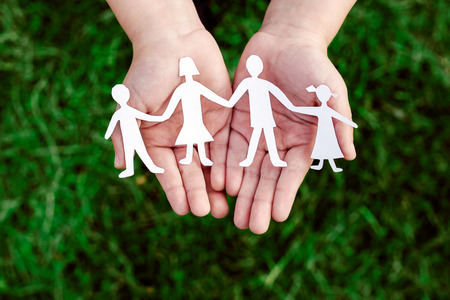 four little men in caring hands Stock Photo