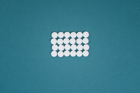 the photo of white tablets and drugs on a blue background