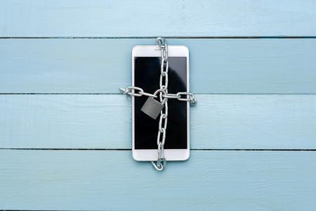 The smartphone is associated with a chain with a lock, on a wooden table