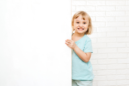 little girl holding a white sign or poster