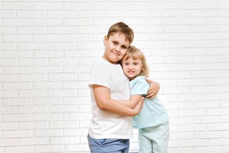 brother and sister hugging against brick sister background