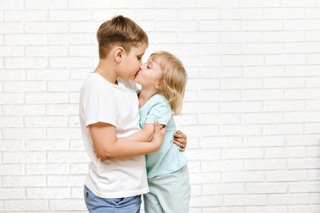 Junge und Mädchen küssen sich vor dem Hintergrund einer weißen Mauer