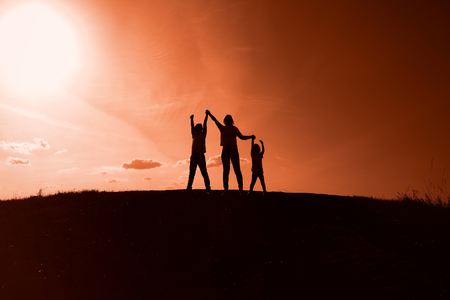 silhouettes of mom, son and daughter on sunset background