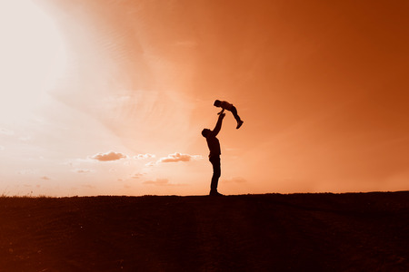 silhouettes of dad and daughter playing on sunset background Banco de Imagens