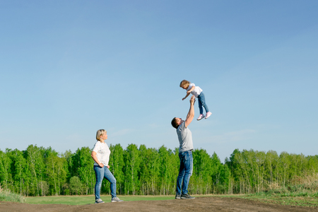 family of three playing in nature