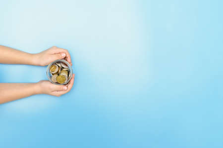 man holding a piggy bank with coins in his hands Stock Photo