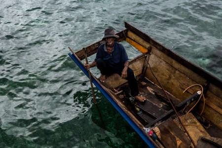 Mabul Island, Sabah, Malaysia - August 08, 2018: A old man with on the small boat, floating on the blue ocean sell seafood for tourist. They are know as
