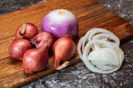 A group of onion on wooden cutting board and black background