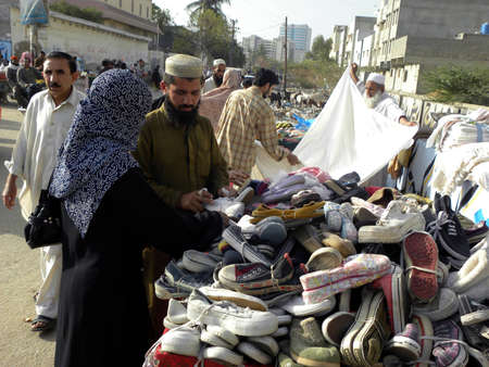 shop keeper: WOMAN_LOCAL YOUNG WOMAN_BUYING USED SHOES AT THE SHOP_IN LOCAL SUNDAY BAZAR_TODAY ON SUNDAY 1132012_KARACHIPAKISTAN