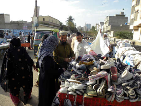 karachi:  WOMAN_LOCAL YOUNG WOMAN_BUYING USED SHOES AT THE SHOP_IN LOCAL SUNDAY BAZAR_TODAY ON SUNDAY 1132012_KARACHIPAKISTAN