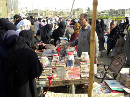 karachi: LOCAL WOMENS_BUYING AN READING_OLD AN USED BOOK AT THE SHOP IN SUNDAY BAZAR TODAY ON SUNDAY 1132012_KARACHI PAKISTAN