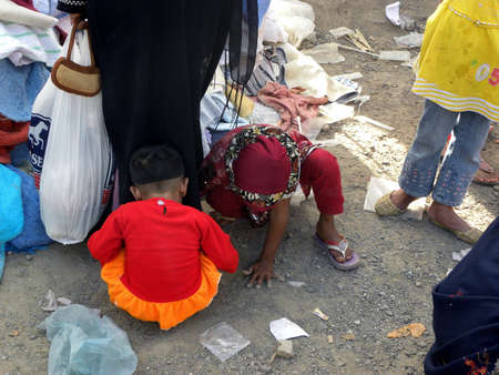 KIDS_PLAYING_ IN DUST IN MARKET TODAY ON SUNDAY_ 1132012_ KARACHIPAKISTAN                                 Editorial
