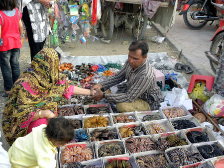 shop keeper: LOCAL WOMAN_BUYING BANGLES FOR HER SIZE_ AND THE SHOP KEEPER WEARING HER SIZE_TODAY ON MONDAY 1232012_ KARACHIPAKISTAN