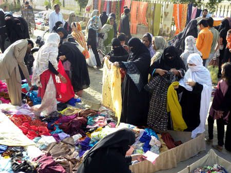 karachi: LOCAL_WOMENS CHECKING AND_BUYING_FABRIC AT THE SHOP_ IN MARKET_TODAY ON MONDAY 1232012_ KARACHI_PAKISTAN                               Editorial