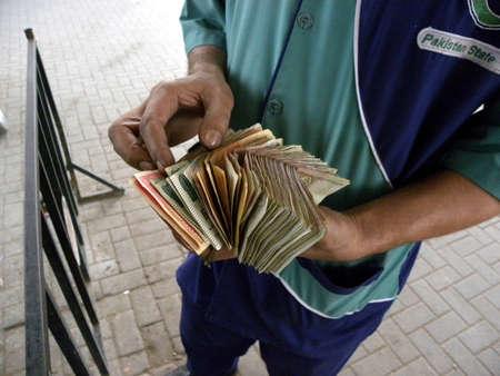 LOCAL_PETROL_PUMP_CASHIER_COUNTING_MONEY TODAY ON THURSDAY_1532012_KARACHIPAKISTAN                               Editorial