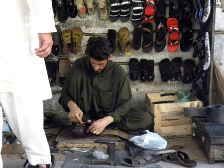 PAKISTANKARACHI_ LOCAL MAN REPAIRING  SHOES BY HAND ON FOOTPATH TODAY ON SUNDAY 25 MARCH 2012                               Editorial
