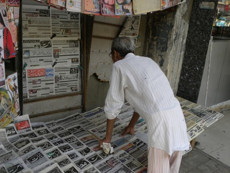 PAKISTANKARACHI LOCAL OLD MAN READING NEWS PAPER AT  THE NEWS PAER SHOP TODAY ON TUESDAY 27 MARCH 2012