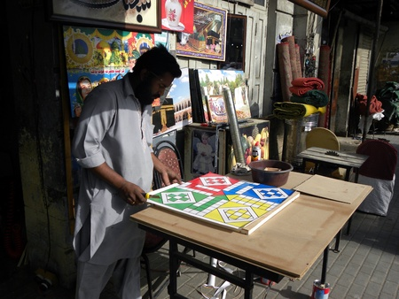 PAKISTAN/KARACHI_MAN MAKING LOCAL INDOOR GAME LUDDO BOARD GAME TODAY ON WEDNESDAY 28 MARCH 2012                           Stock Photo - 12849385