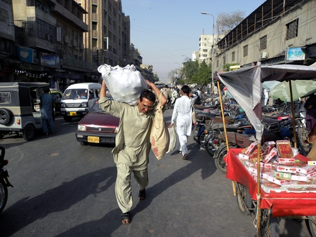 PAKISTANKARACHI_MAN CARRYING A HEAVY LOAD OF GOODS ON HIS SHOULDER IN BOLTAN MARKET TODAY ON MONDAY 9 APRIL 2012